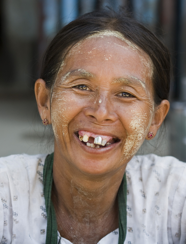 A Myanmar market woman flashes her smile with a big silver tooth.